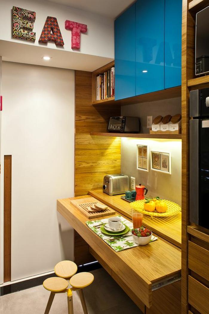 petite cuisine équipée avec grande inscription colorée MANGE au mur, espace de rangement en bleu turquoise, petit tabouret en style excentrique constitue de trois ronds