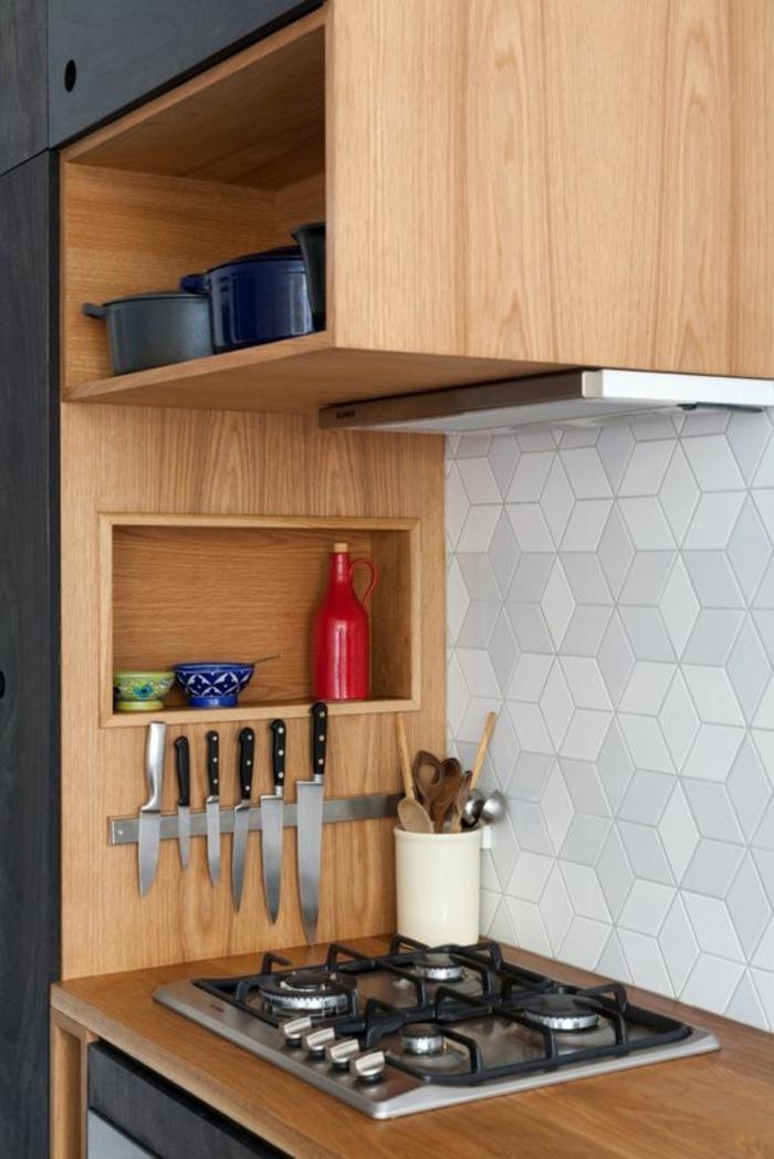 amenagement petite cuisine, petite cuisine équipée avec des grandes casseroles en couleurs différentes, couteaux de taille différente suspendus au mur, près des fourneaux, crédence en blanc et gris avec des dalles en forme de ruches