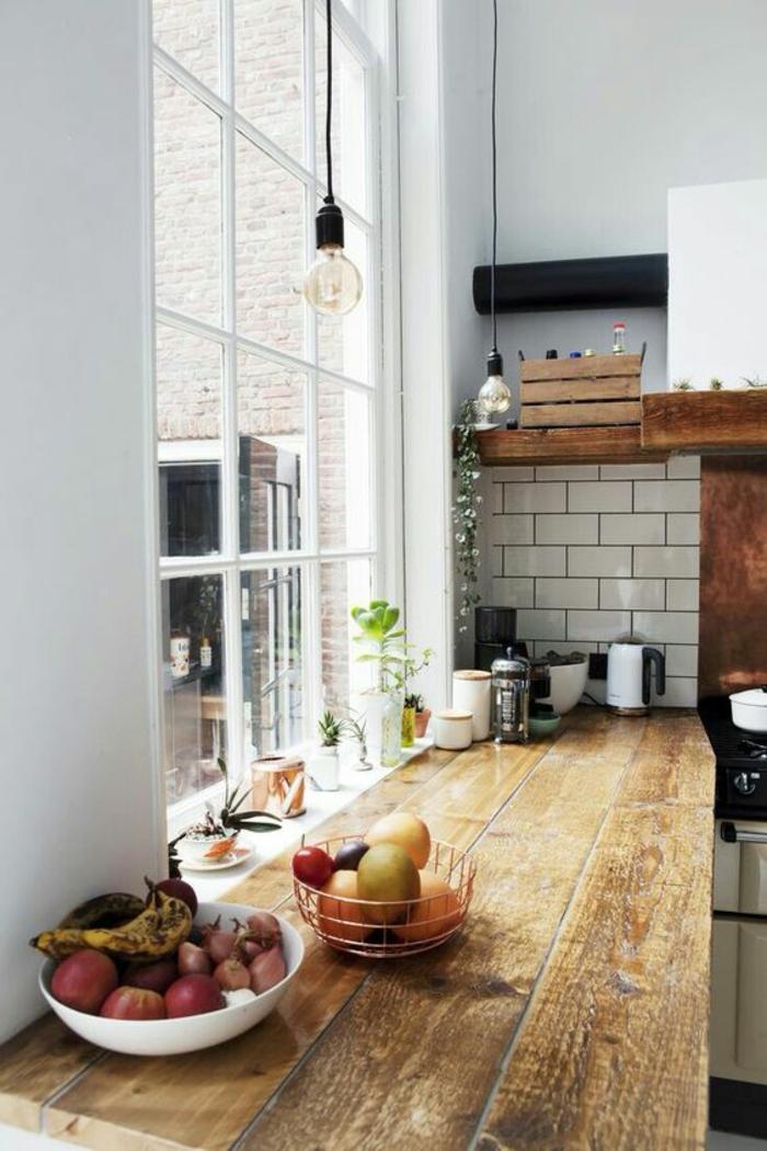 amenagement petite cuisine, crédence en briques blanches, plan de travail en lambris en bois rude aux nuances chaudes marron et jaune, luminaires ampoules nues suspendues avec du fil noir
