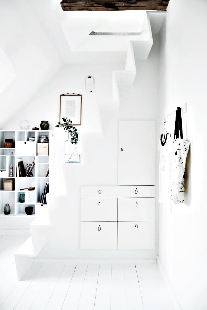 couloir blanc avec petit escalier minimaliste et rangement sous pente en armoires blanches