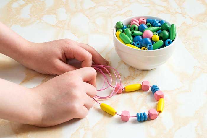 comment faire un collier avec des ornements colorés enfilés sur un fil rose, activités montessori créatives, développement de la motricité fine