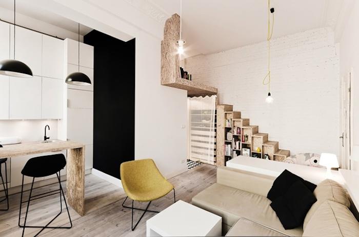 pan de mur en ardoise murale avec meuble de cuisine blanc, parquet bois brut, canapé gris clair, escalier bois