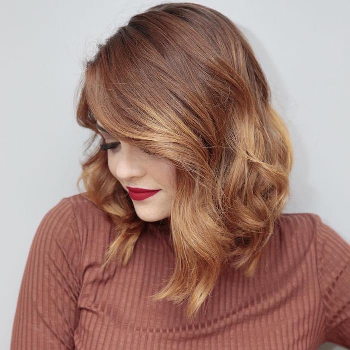 exemple de coiffure carré plongeant avec des mèches longues sur le devant, cheveux couleur cuivre, pull rouge marron