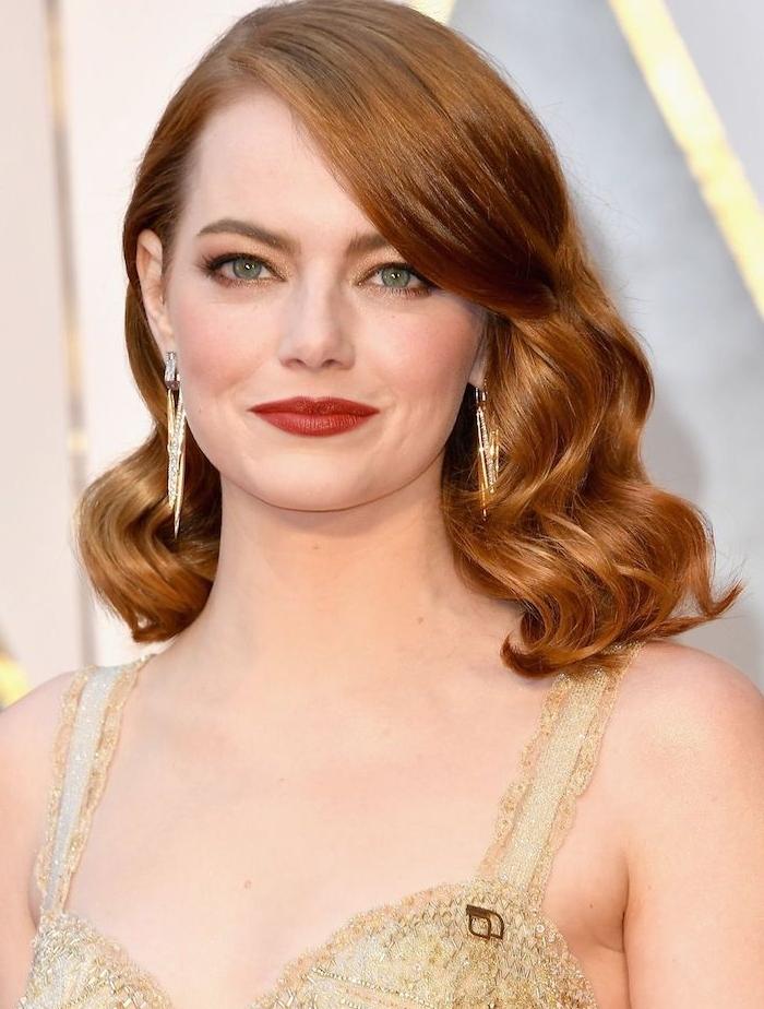 carré long bouclé avec des boucles vintage sur des cheveux roux femme, robe couleur or, emma stone look tapis rouge