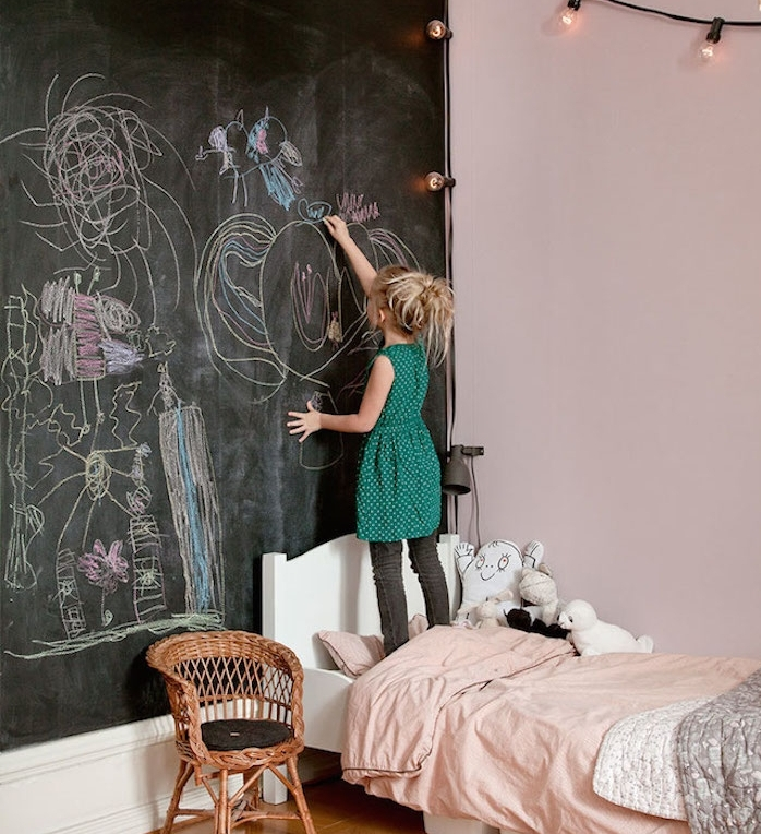 exemple de chambre enfant fille avec un mur de fond en peinture ardoise avec des dessins à la craie, lit blanc aux draps rose, chaise en rotin