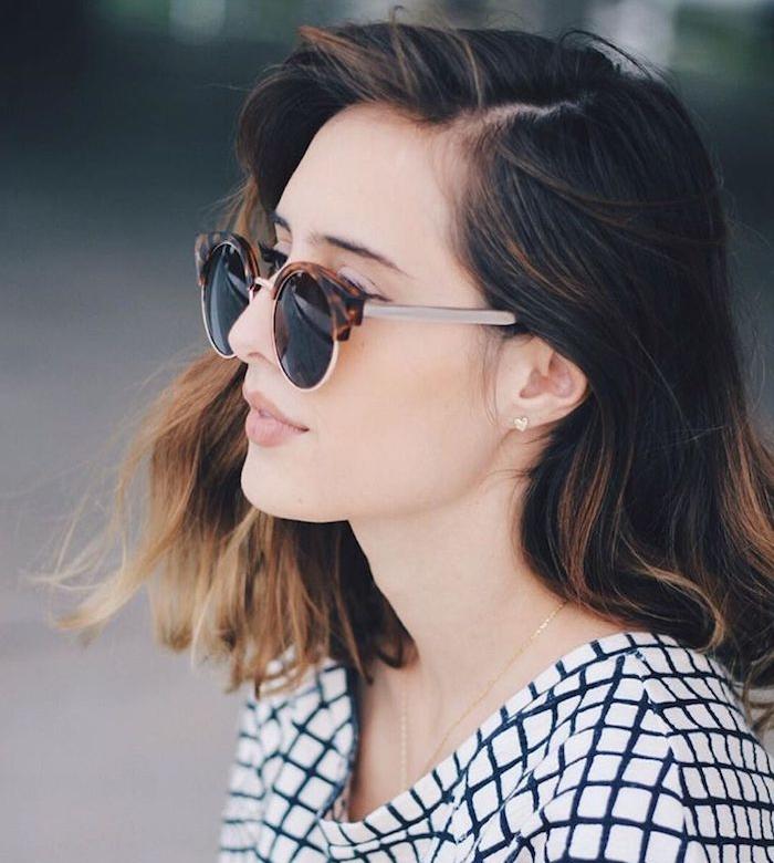 carré plongeant dégradé avec plus de longueur sur le devant et des mèches blond foncé dans des cheveux chatain, robe blanc et noir, lunettes de soleil