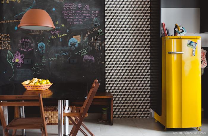 exemple de cuisine aménagée aux accents vintage, frigo jaune, mur en peinture gris ardoise, table noir et blanc et chaises bois marron foncé, dessins à la craie