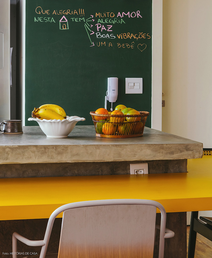amenagement cuisine moderne avec un pan de mur en peinture à la craie, notes importantes écrites à la craie, ilot central beton original