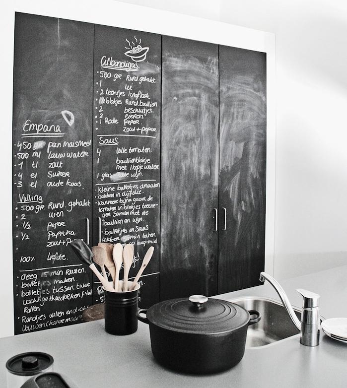 exemple de cuisine equipée avec portes armoire en ardoise murale avec des recettes écrites à la craie et ustensiles de cuisine noires