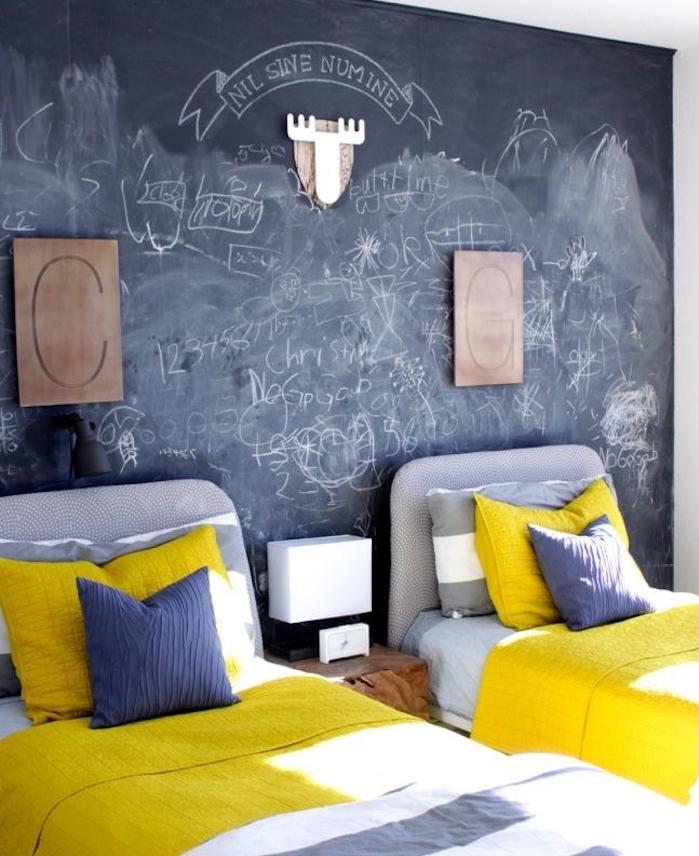 exemple de déco chambre enfant double avec des lits gris et linge de lit gris et blanc, mur en ardoise murale avec des gribouillis