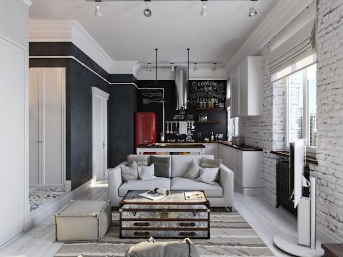 amenagement salon ouvert sur cuisine avec murs tableau ardoise, meuble bas blanc à plan de travail bois foncé, mur en briques, salon vintage, table en coffre et canapé gris clair