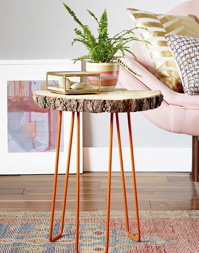 modele de table basse bois brut avec des pieds en metal orange et plateau en rondin de bois, accent rustique dans un salon feminin, canapé rose