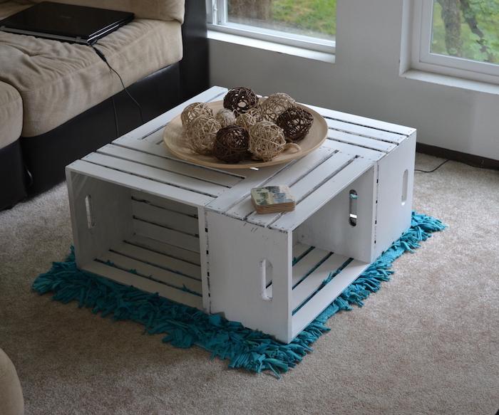 table basse caisse pomme, des cagettes de bois repeint en blanc et assemblées, tapis bleu à franges, canapé noir et beige