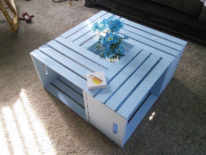 table basse caisse pomme fabriquée à partir de quatre cagettes blanchies, tapis gris, bouquet de fleurs au centre