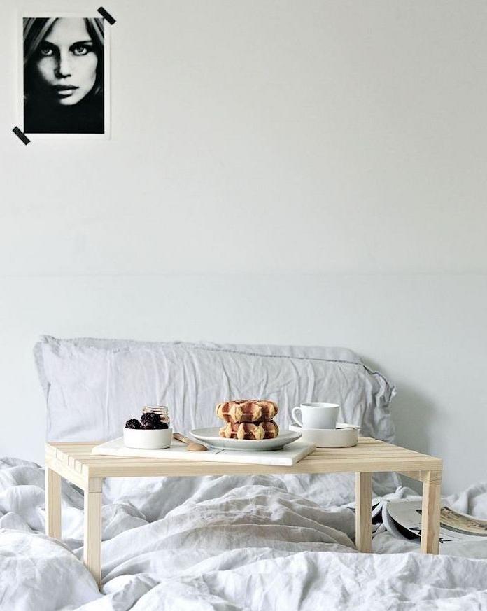 exemple de table basse diy de lit en lattes de bois clair sur un linge de lit gris, deco murale portrait noir et blanc femme
