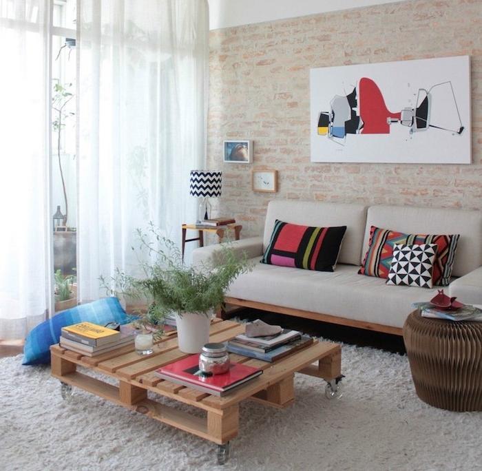 table basse en palette de bois sur roulettes, canapé en bois avec coussin d assise blanc cassé, tapis moelleux, mur aspect briques