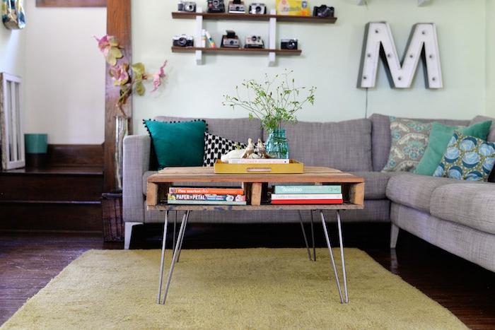 faire une table basse palette de bois avec des pieds en epingle a cheveux, canapé d angle gris et coussins en bleu, vert et gris