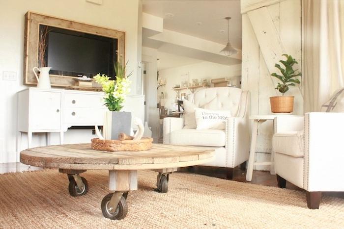 modele de table basse touret en plateau de bois sur roulettes, tapis beige, fauteuils blancs, deco style campagne rustique