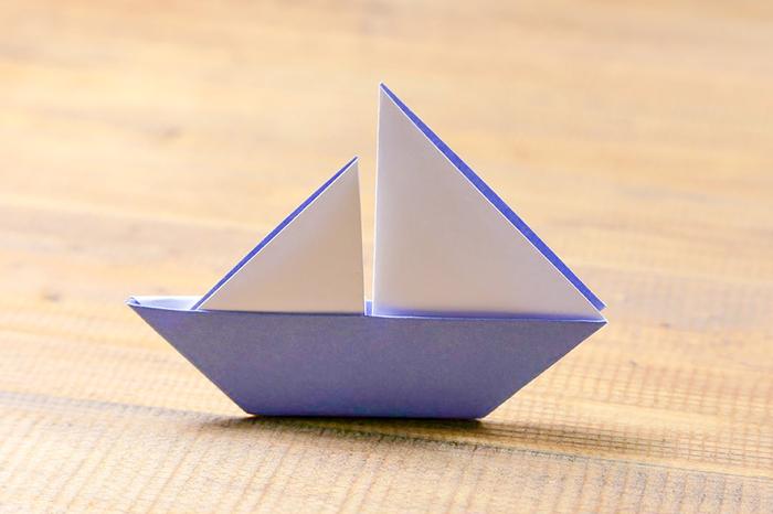 un modèle d'origami bateau à voile réaliser en peu de temps avec une simple feuille de papier coloré