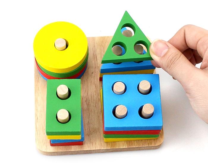 jeu d association, rangement de figures geometriques colorées sur une planche en bois, pédagogie montessori en crèche