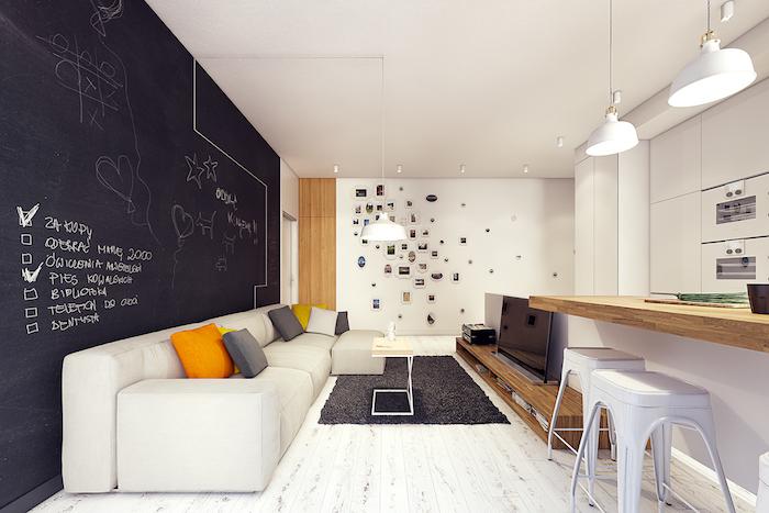 cuisine ouverte sur salon avec un mur décoré de peinture ardoise, dessins et texte à la craie, parquet blanchi, ilot central plan de travail bois, mur de photos, canapé blanc cassé