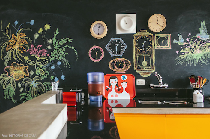 améangement cuisine en noir et jaune avec meuble bas en jaune et plan de travail noir, mur à la peinture craie et dessins de fleurs et horloges