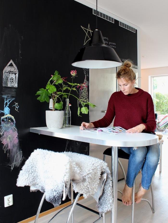 peinture ardoise sur un mur dans la cuisine, petite table ilot inox, chaise avec jeté scandinave, dessins enfan, suspension noire