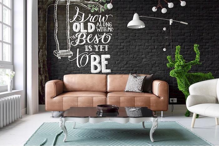 deco style industriel dans un salon avec canapé marron en cuir, table basse noir et blanc, mur en briques couvert de parement ardoise, figurine cerf en buis