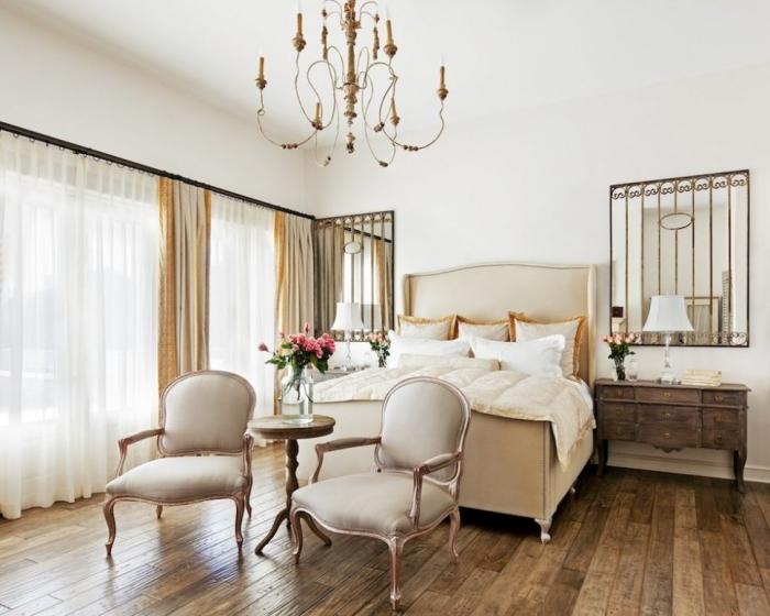 grandes fenêtres avec rideaux longs dans une chambre a coucher adulte aux murs blancs et décoration beige