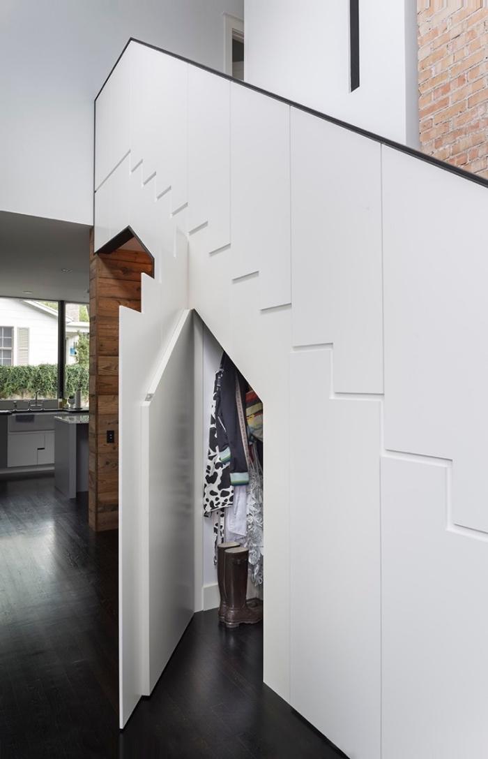 intérieur au mur briques rouges et plancher foncé avec rangement sous escalier coulissant blanc