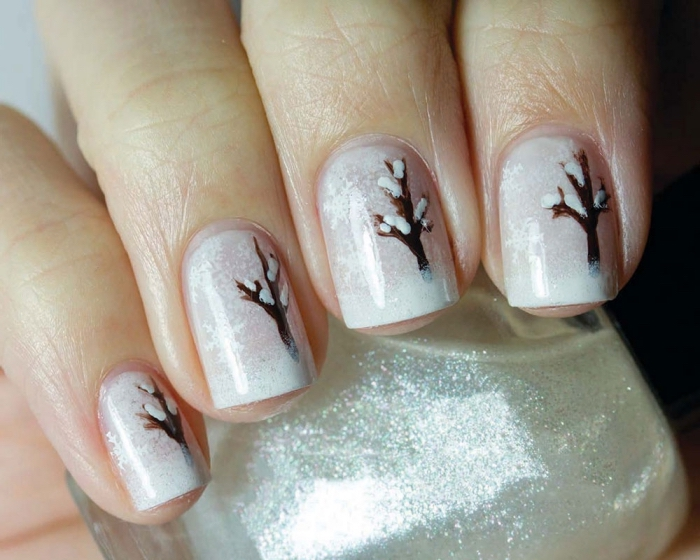 idée pour décoration ongles de Noel avec base blanche à effet enneigé et dessin d'arbre marron