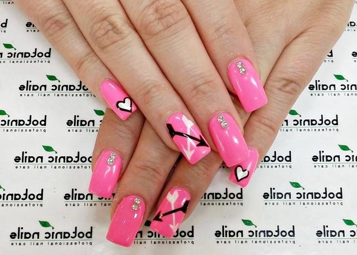 extensions et capsules en gel pour avoir ongles longs, vernis gel de couleur rose avec dessin en blanc et noir