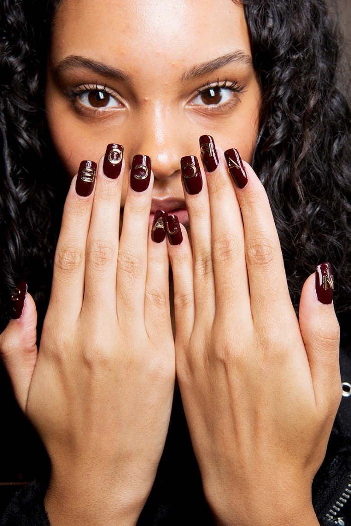 jolies mains à ongle manicure bordeaux avec décoration à symboles de nuance dorée, extensions en gel pour ongles longs