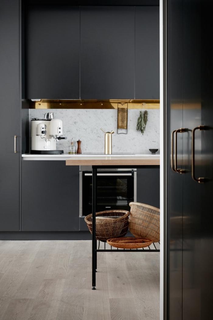 parquet stratifié de bois clair dans une cuisine à meubles noir matte avec crédence à design marbre blanc