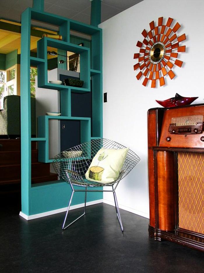 étagère de séparation en bleu pétrole, avec deux grandes formes rectangulaires, sol en gris graphite, radio en style rétro