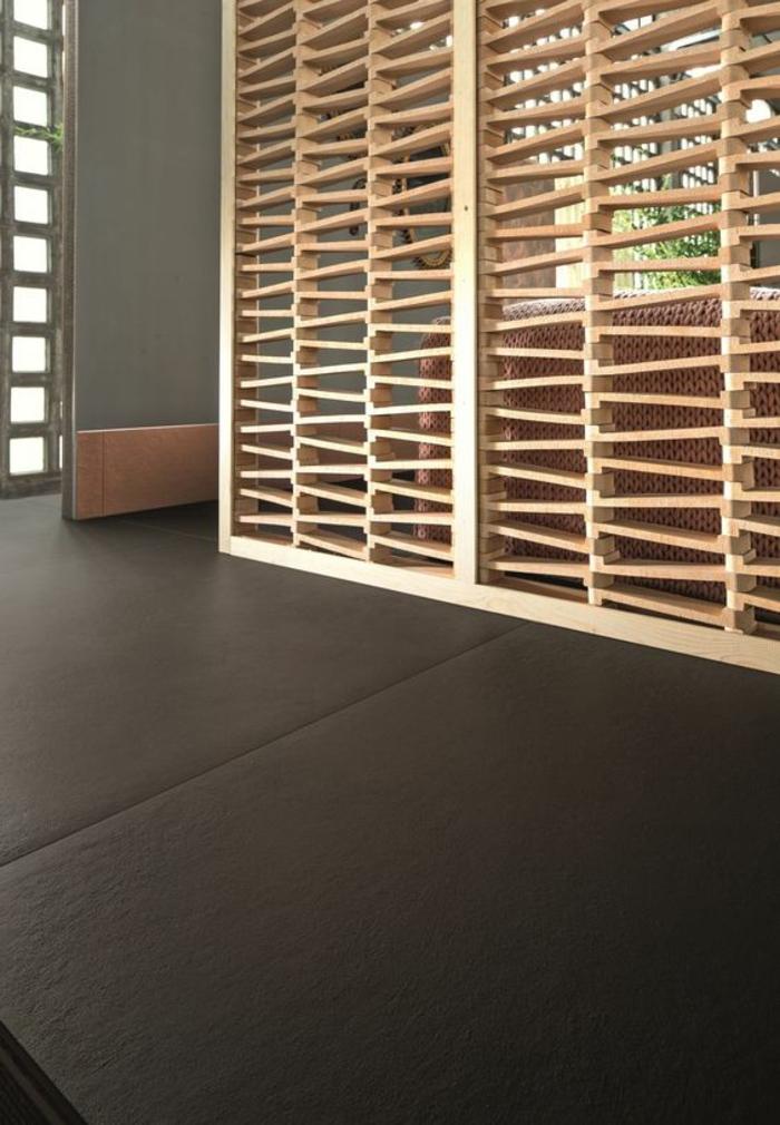 panneau en bois clair, avec des multiples ouvertures, effets ajourés, separateur de piece avec sol en couleur gris anthracite