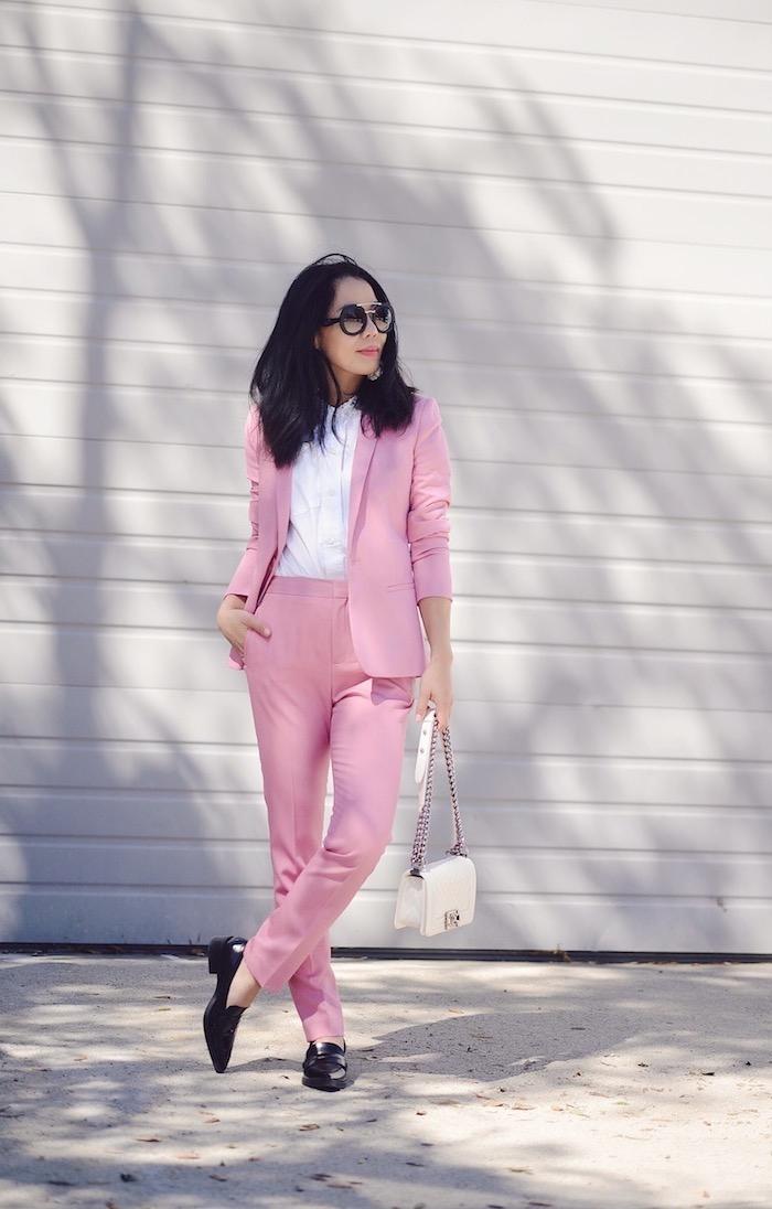 tailleur pantalon femme chic en rose pastel avec chemise blanche et des mocassins noirs pour un look professionnel et féminin