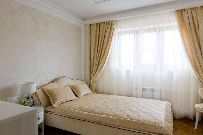 aménagement simple dans la chambre à coucher avec rideaux jaune et meubles de cuir beige