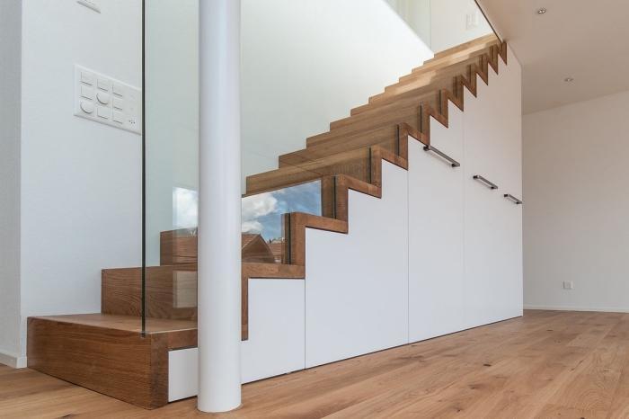 rangement sous escalier blanc avec poignées métalliques, couloir aux murs blancs et plancher de bois clair