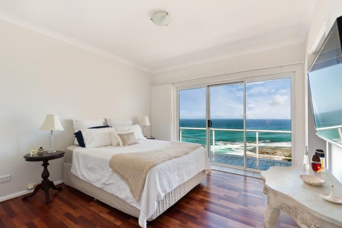 association couleur beige dans une chambre avec vue mer, déco simple et pure avec meubles de bois et grand lit