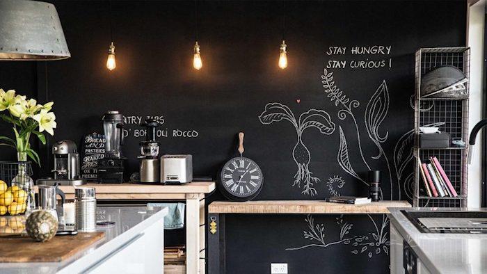 exemple de cuisine avec mur tableau ardoise aux dessins et textes à la craie, meubles bois, metal et inox, luminaires style industriel