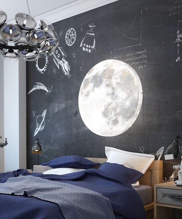 peinture tableau noir sur un mur de fond derrière un lit en bois et linge de lit bleu marine, suspension luminaire original