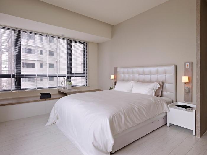 chambre design moderne avec lit kingsize de tête boutonnée, déco minimaliste avec lit et banc de bois sous fenetre