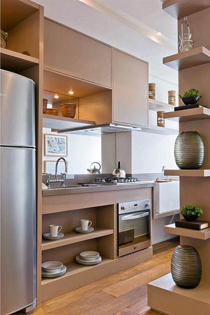 meubles de cuisine, petite cuisine équipée, cuisine petit espace, avec plein d'étagères au mur, sol recouvert de parquet en nuances marron et jaune, frigo haut et large dans une niche