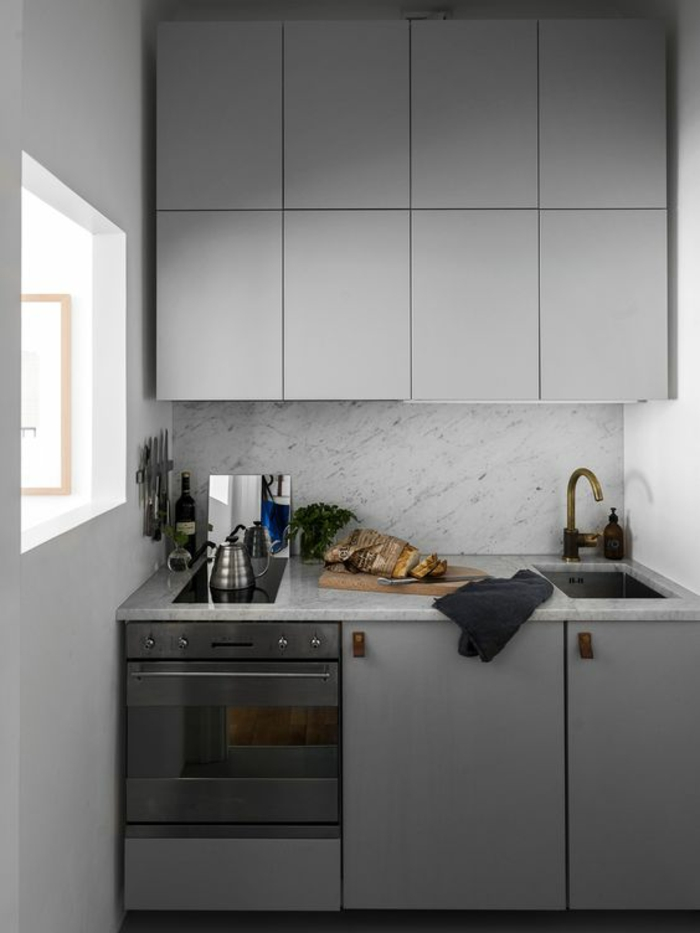 cuisine intégrée avec des meubles en gris perle, petite fenêtre, crédence aux motifs de marbre en noir et blanc, évier du lavabo en couleur bronze, poignées des meubles en plastique marron