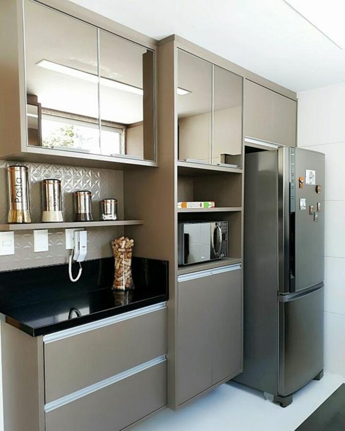 cuisine petit espace, meubles de cuisine en couleur bronze avec plan de travail noir luisant, haut frigo en couleur noire, carrelage blanc