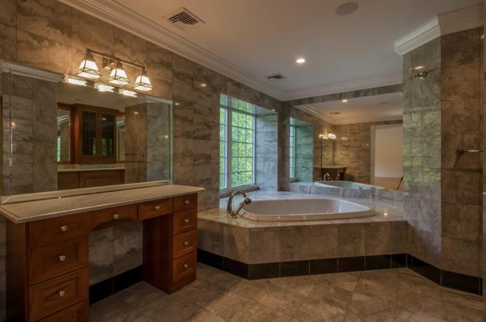 pierre de travertin, grand miroir rectangulaire, applique murale, baignoire d'angle au-dessous de la fenêtre