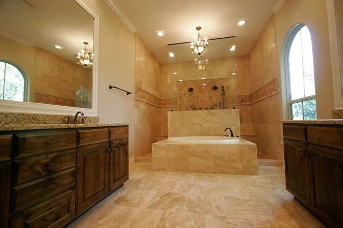 salle d'eau en beige, grande fenêtre arquée, miroir rectangulaire, lustre chandelier