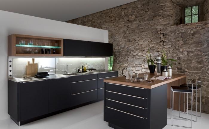 cuisine moderne aux armoires noires matte avec mur blanc et mur en pierres, éclairage led sous meubles de cuisine