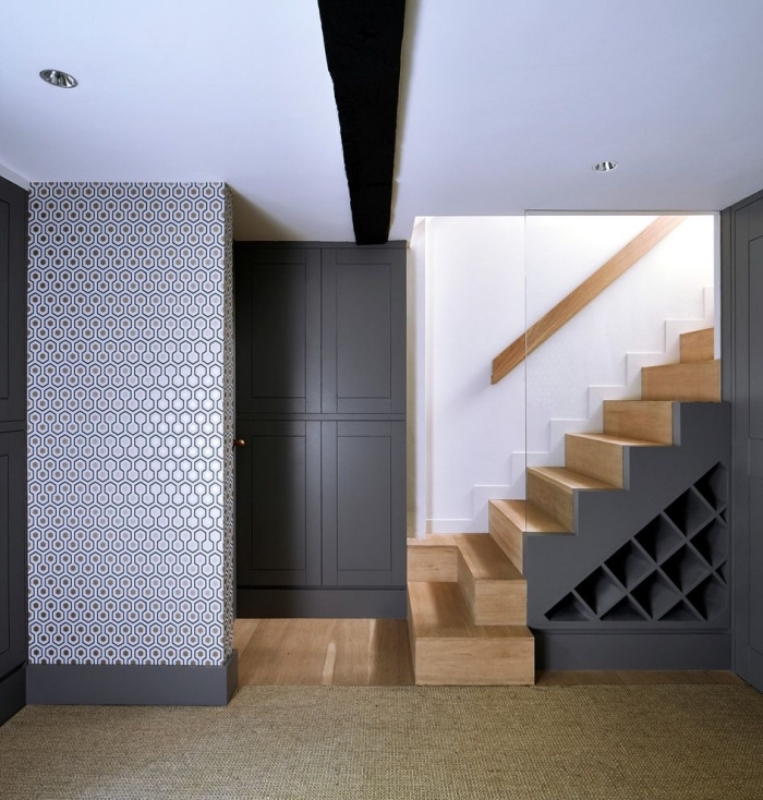 décoration intérieur en blanc noir et bois avec escalier moderne et rangement sous pentes pour bouteilles ou chaussures